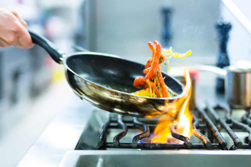 Chef,In,Restaurant,Kitchen,At,Stove,With,Pan,,Doing,Flambe